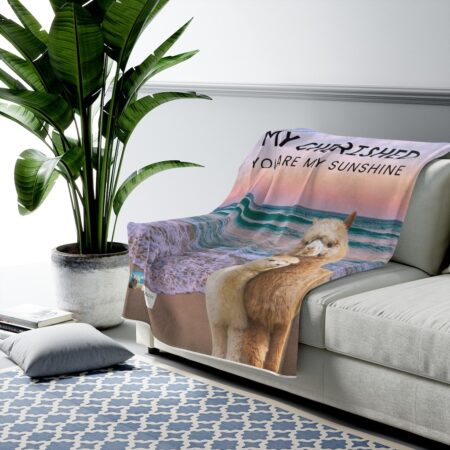 Reviewer holding Cherished baby alpaca beach gift blanket on couch